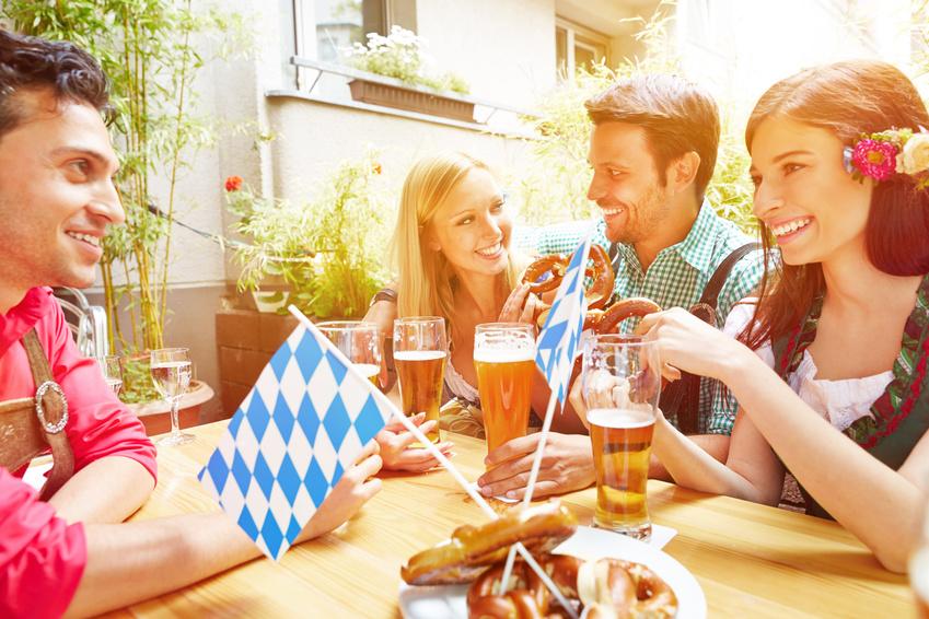 Lachende Freunde haben zusammen Spaß im Biergarten in Bayern